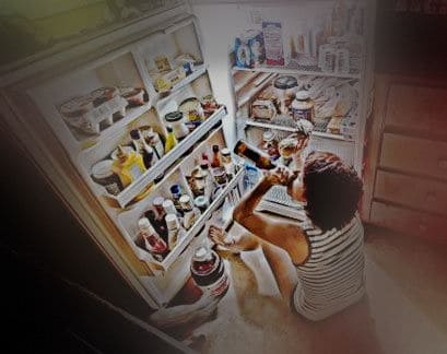 Person sitting in front of refrigerator and drinking from a bottle