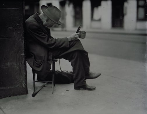 poor man sitting hunched over on a sidewalk