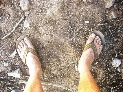 dusty feet in flip-flops on a dusty road