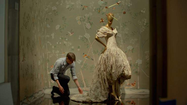 Man adjusting the train on a mannequin's dress
