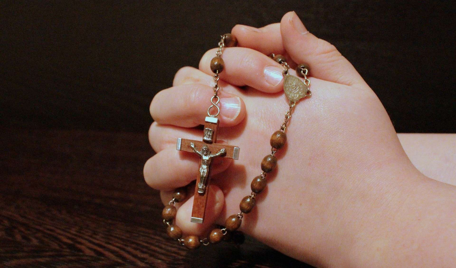 Folded hands holding a rosary