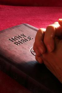 hands folded in prayer on Holy Bible